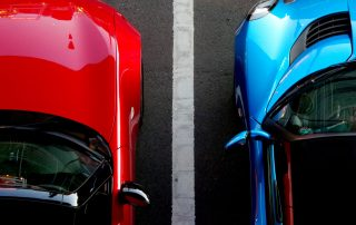 blue and red cars parked next to each other
