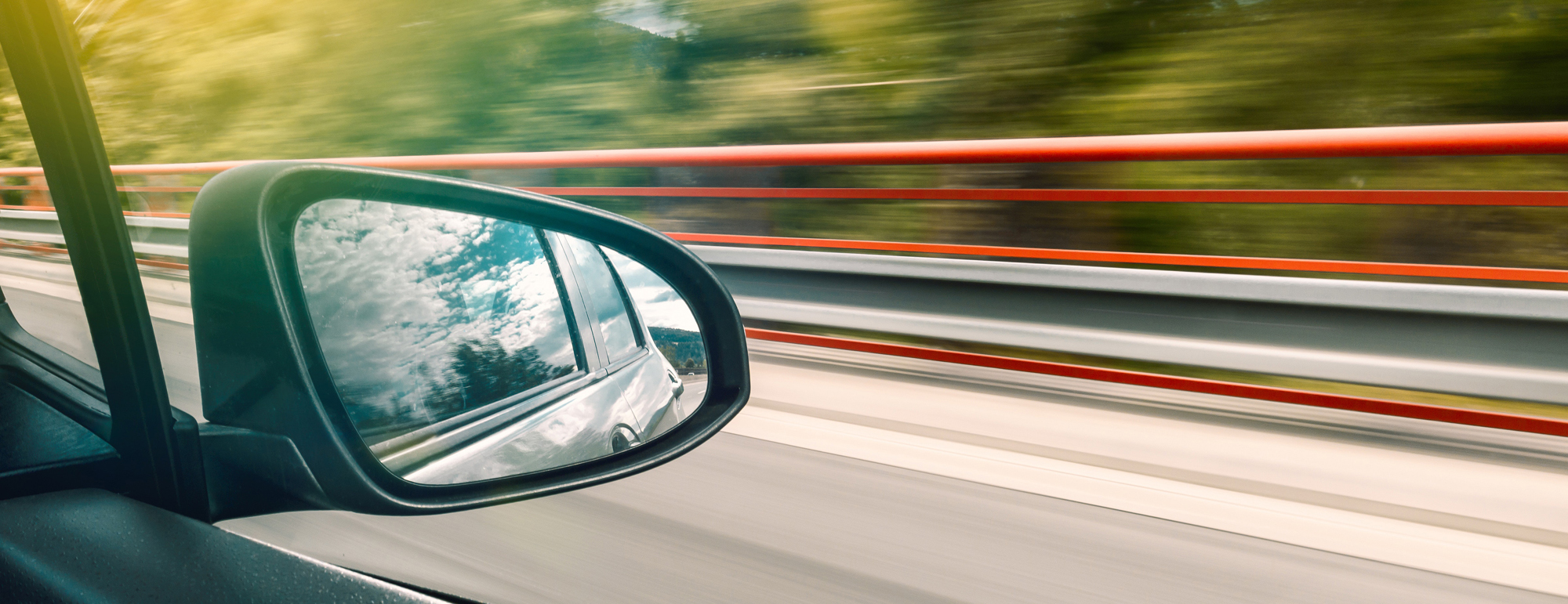 side mirror of a car while driving down the road